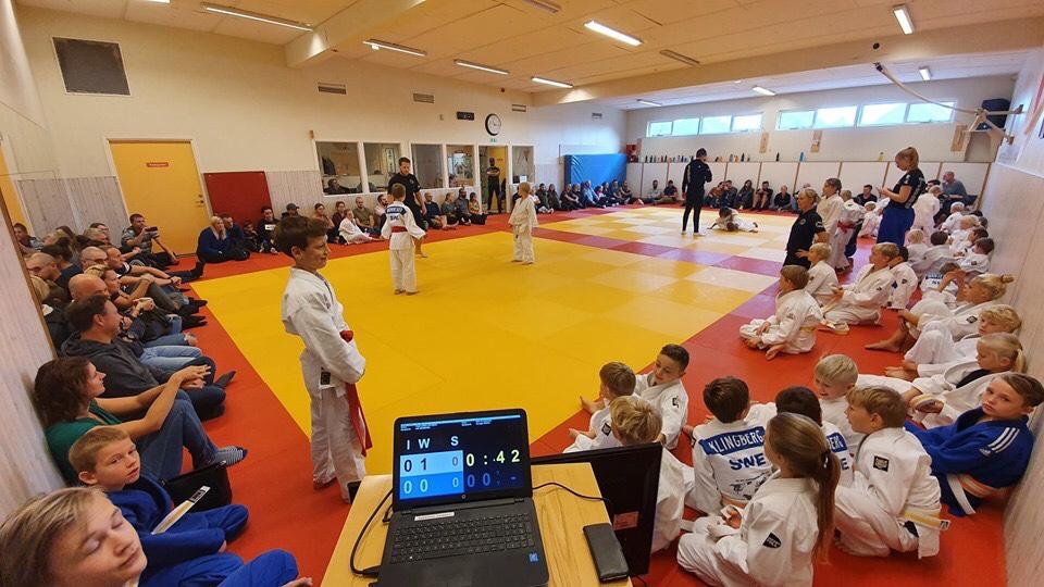 Myntjakten i Staffanstorps judoklubb. En massa människor som sitter runt två judomattor. Två yngre barn tävlar mot varandra.