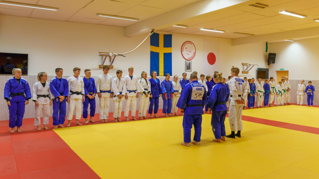 Judoka som är uppställda och fyller hela mattkanten i dojon